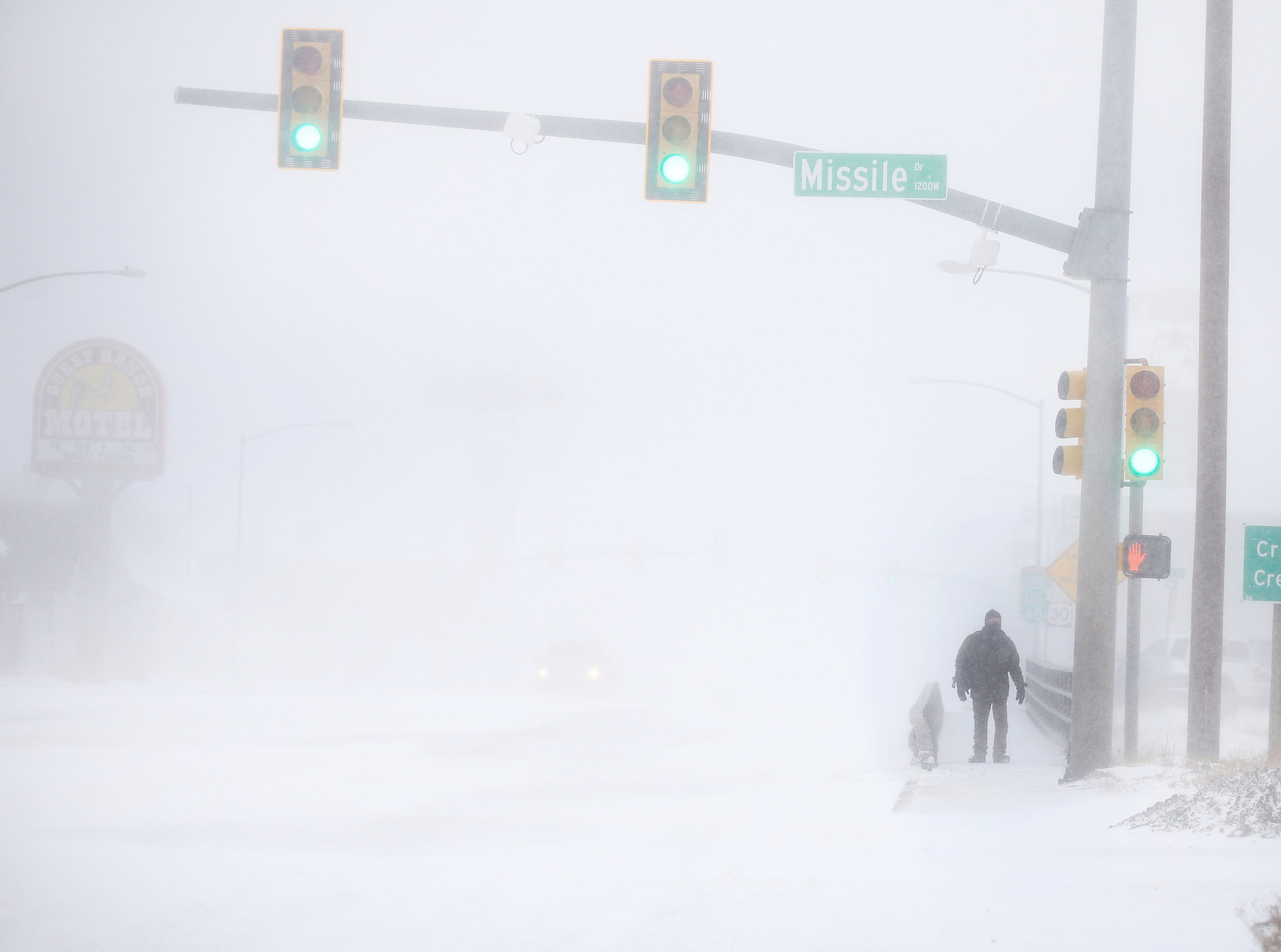 James Little crosses the street during a blizzard on Wednesday, March 13, 2019, in Cheyenne, Wyo.  Heavy snow hit Cheyenne about mid-morning Wednesday and was spreading into Colorado and Nebraska.