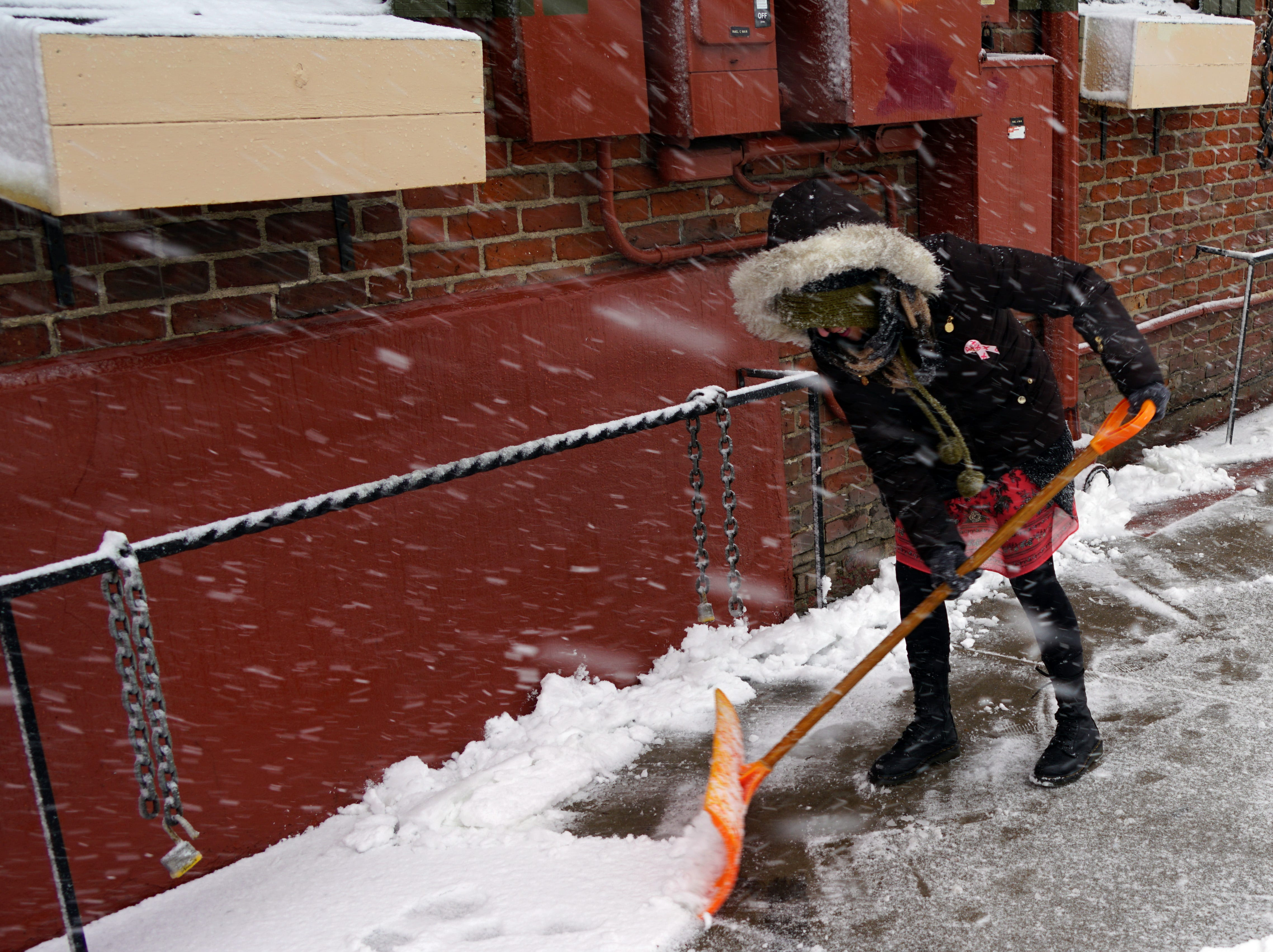 """Head bent against the driving snow, Rindi Gray, 48, shovels the sidewalk outside Denver's """"My  Brothers Bar,"""" during a blizzard, March 13, 2019."""