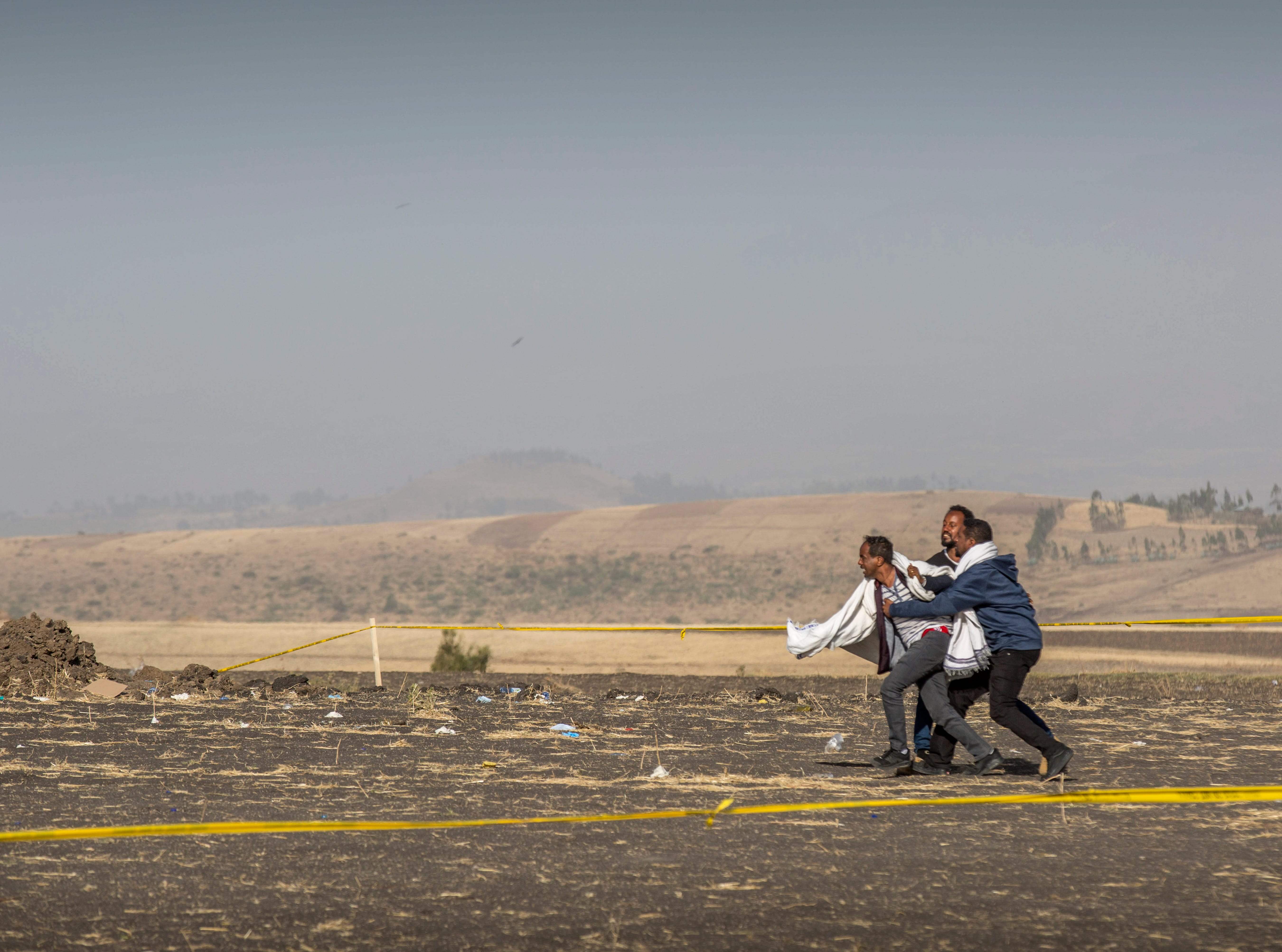 A grieving relative is held back by others at the scene where the Ethiopian Airlines Boeing 737 Max 8 crashed shortly after takeoff on Sunday killing all 157 on board, near Bishoftu, or Debre Zeit, south of Addis Ababa, in Ethiopia Wednesday, March 13, 2019.