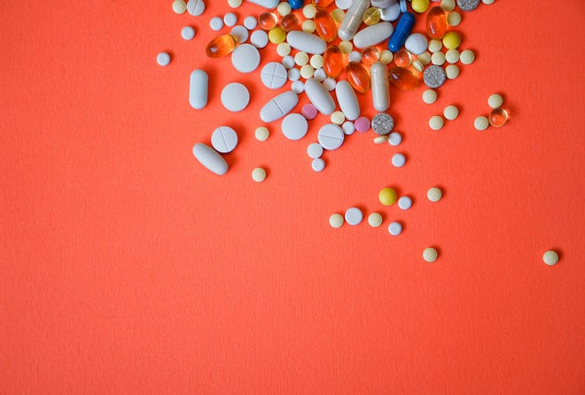 Assorted pharmaceutical medicine pills, tablets and capsules and bottle on red background. Drugs and various narcotic substances. Copy space for text. Stock photo for design