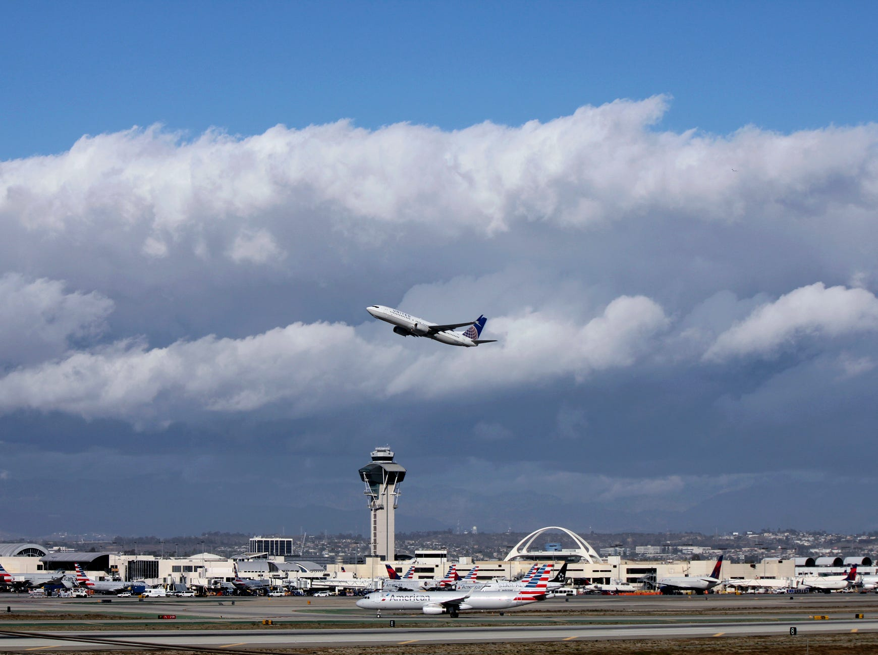 In this file photo, a plane flies over Los Angeles International Airport. The Los Angeles County Department of Public Health is warning travelers that a person with measles was at the airport last month.