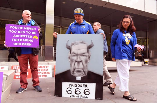 Survivors of church abuse hold placards outside at the County Court to hear the sentencing of Cardinal George Pell who was was found guilty on historic child sex crimes, in Melbourne on March 13, 2019.