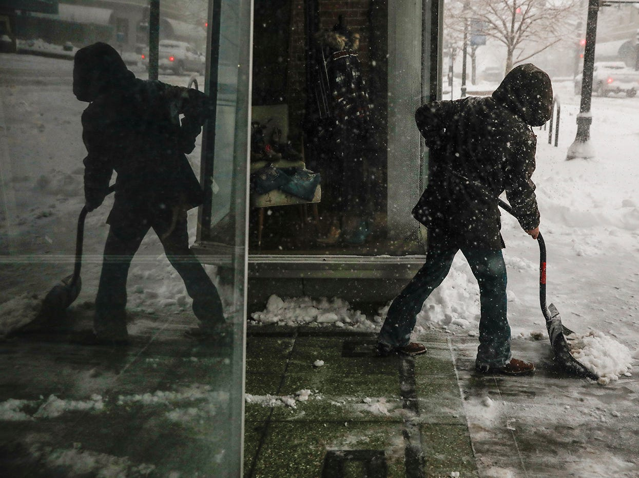 Riley Dennis shovels snow from the sidewalk March 13, 2019 during a winter storm in Casper, Wyo.