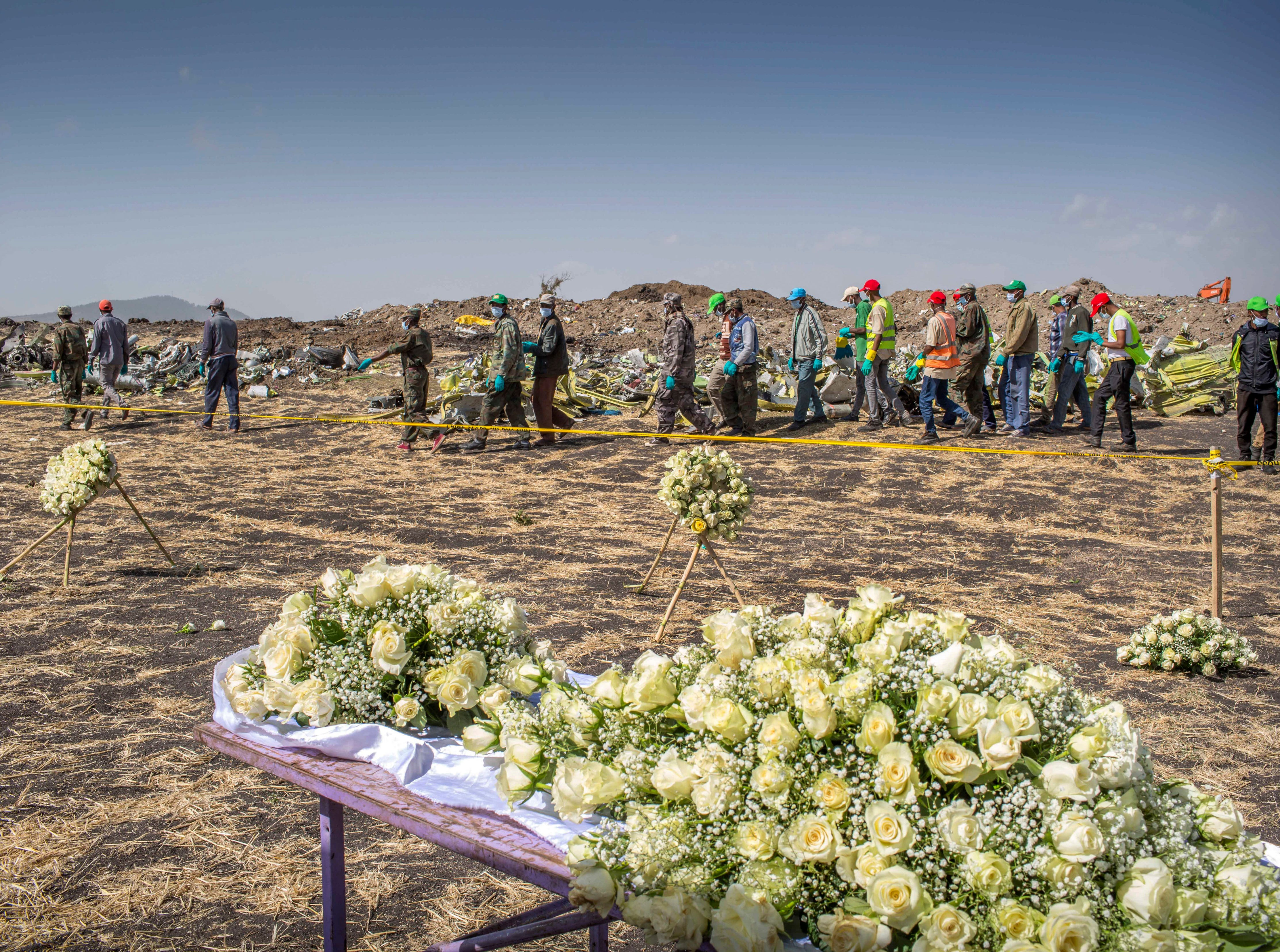 Workers walk past flowers laid at the scene where the Ethiopian Airlines Boeing 737 Max 8 crashed shortly after takeoff on Sunday killing all 157 on board.