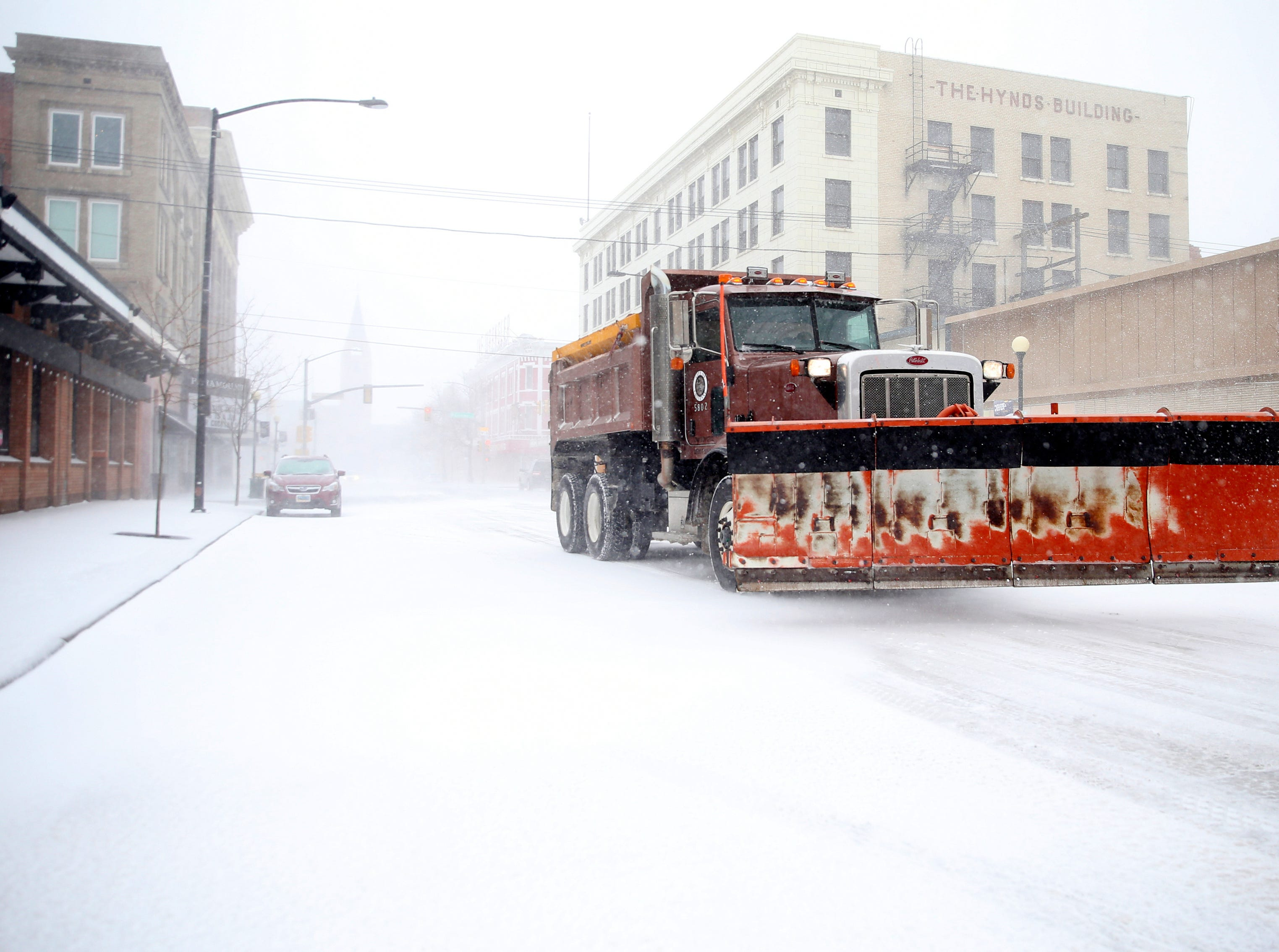 A snow plow rumbles north on Capitol Avenue during a blizzard March 13, 2019, in Cheyenne, Wyo.