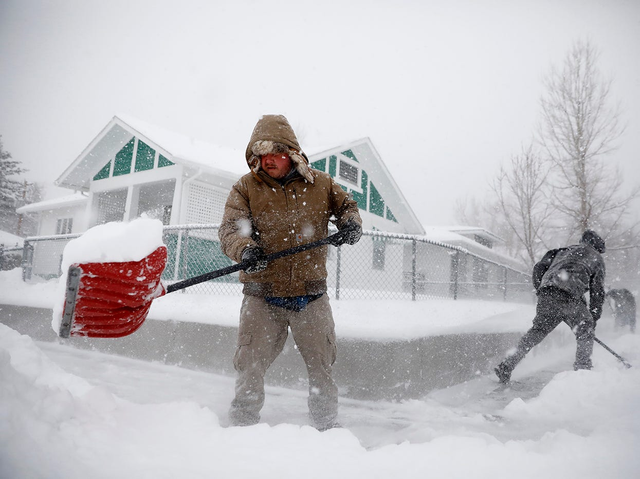 Martin Thompson clears snow from the sidewalk Wednesday,  March 13, 2019 during a winter storm in Casper, Wyo.