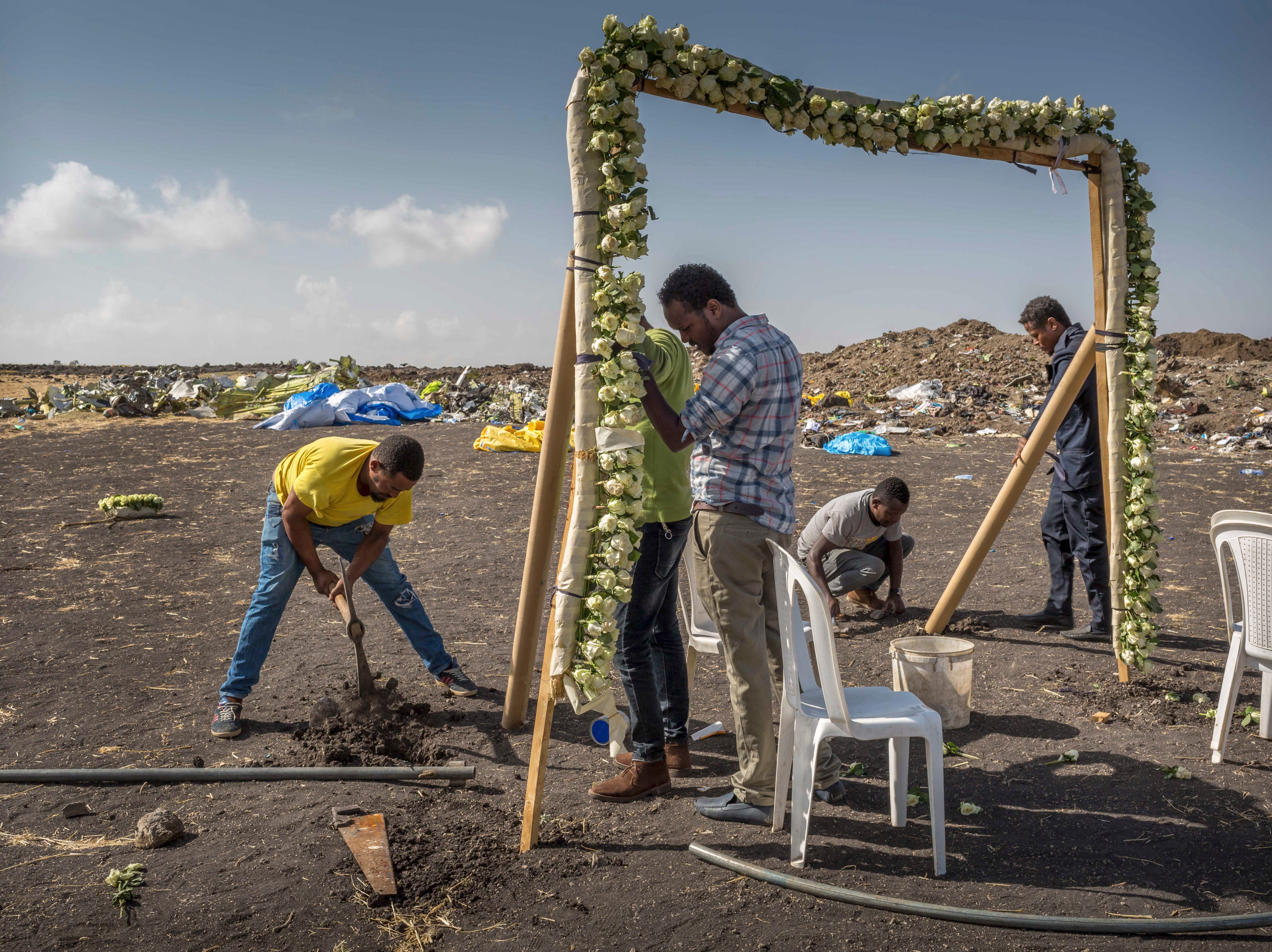 Workers erect a floral installation at the scene where the Ethiopian Airlines Boeing 737 Max 8 crashed.