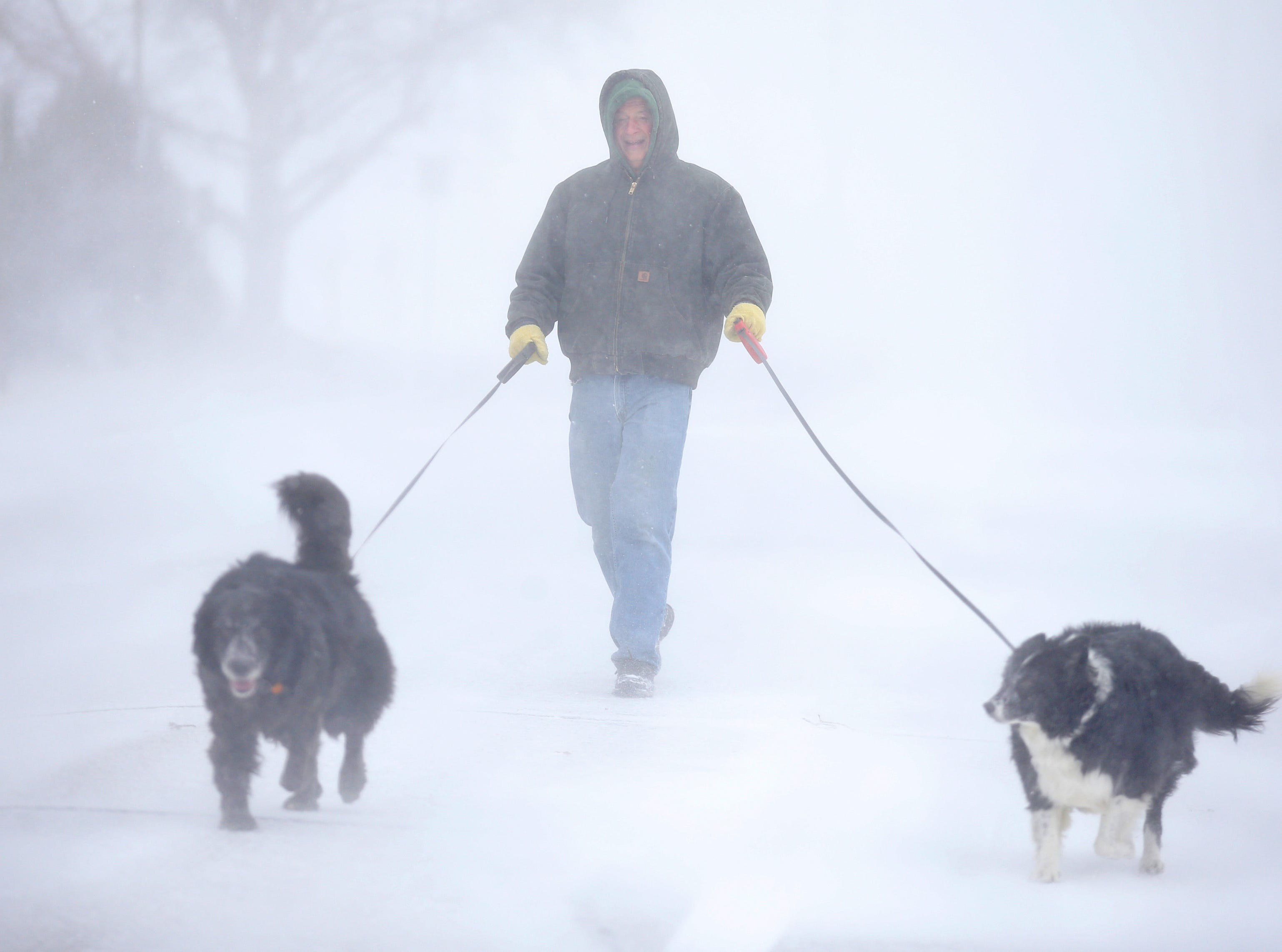 Tom Skaar laughs while walking his dogs during a blizzard March 13, 2019, in Cheyenne, Wyo. White-out conditions closed I-80, I-25, and U.S. 85, effectively closing off the state capital from Nebraska, Colorado and the rest of Wyoming.