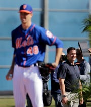 Mets general manager Brodie Van Wagenen, right, watches as Mets pitcher Jacob deGrom, left, prepares to throw a pitch.
