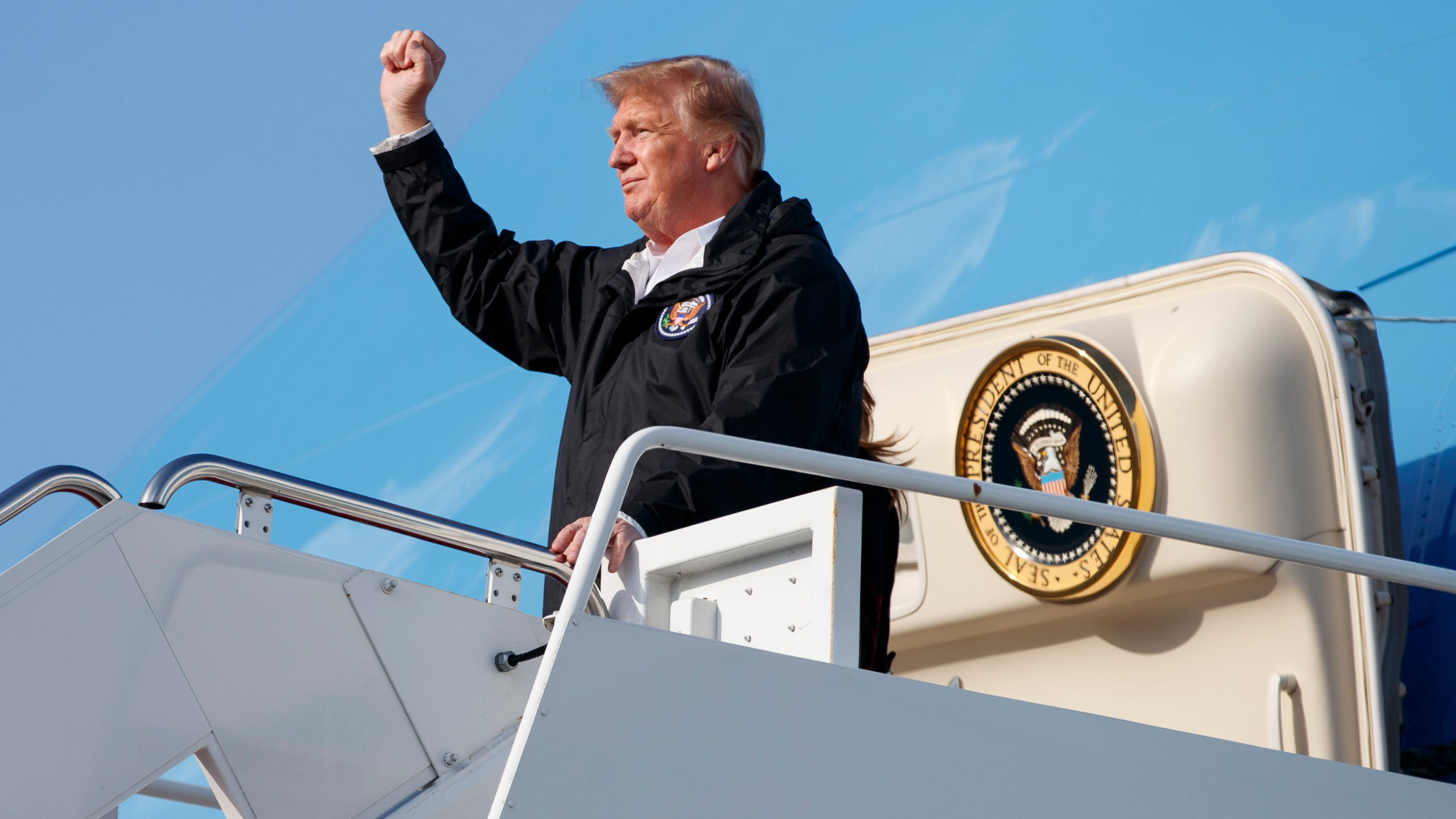 President Donald Trump gestures from Air Force One at Palm Beach International Airport on March 8, 2019.
