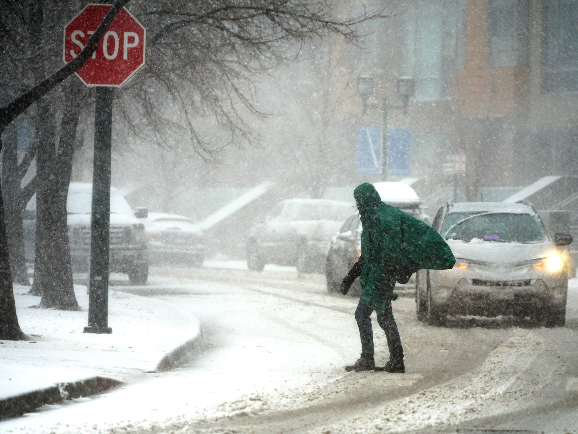 A pedestrian crosses the street in downtown Denver, March 13, 2019, during a blizzard.