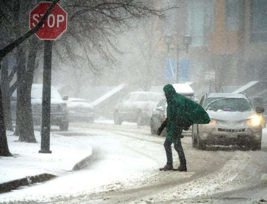 A pedestrian crosses the street in downtown Denver on March 13, 2019, during a blizzard. Yet another snowstorm is forecast to paste the central U.S. this week.