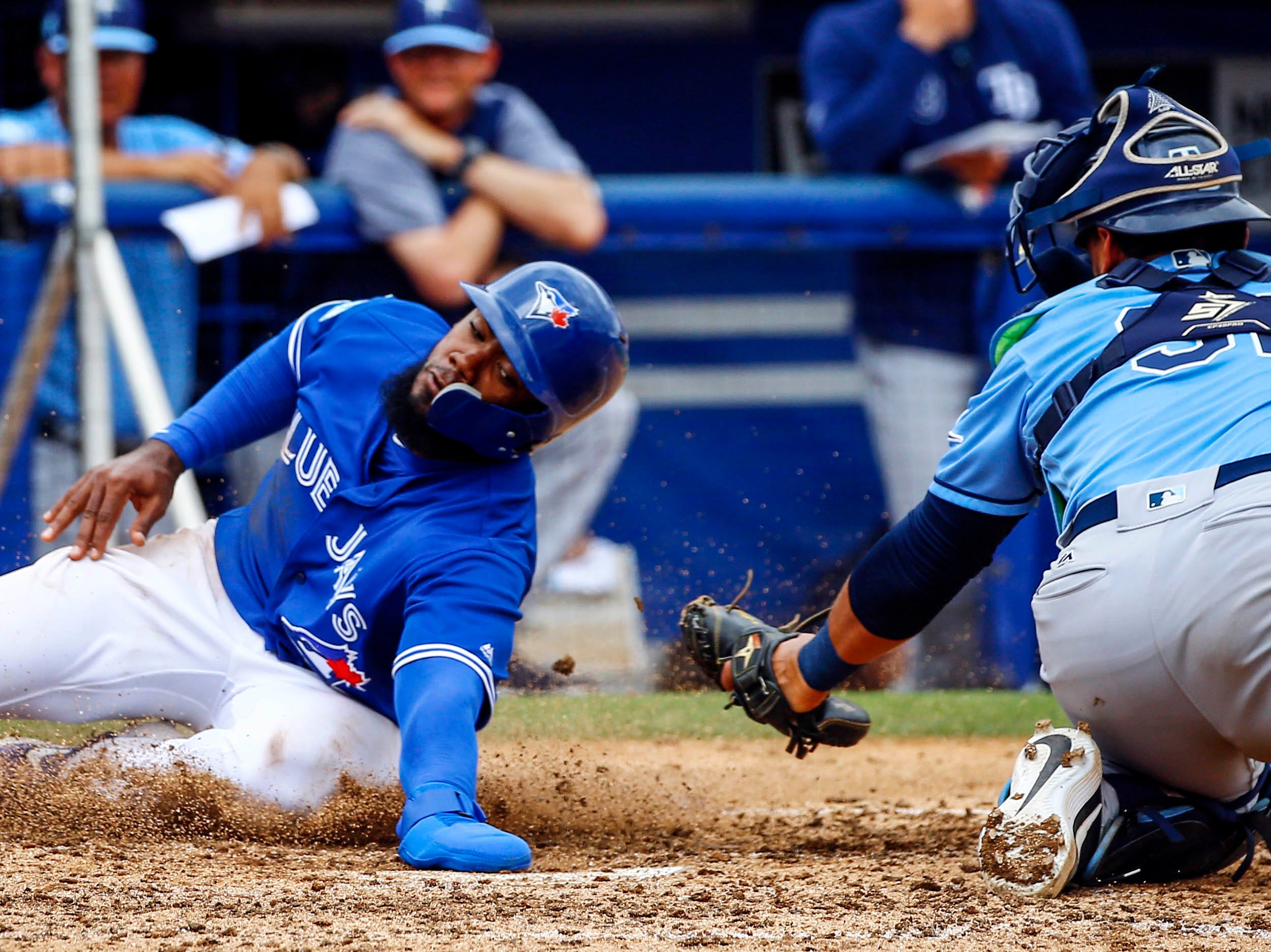 March 12: Blue Jays outfielder Teoscar Hernandez scores ahead of the tag from Rays catcher Rene Pinto.