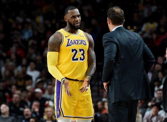 Los Angeles Lakers forward LeBron James speaks with head coach Luke Walton.