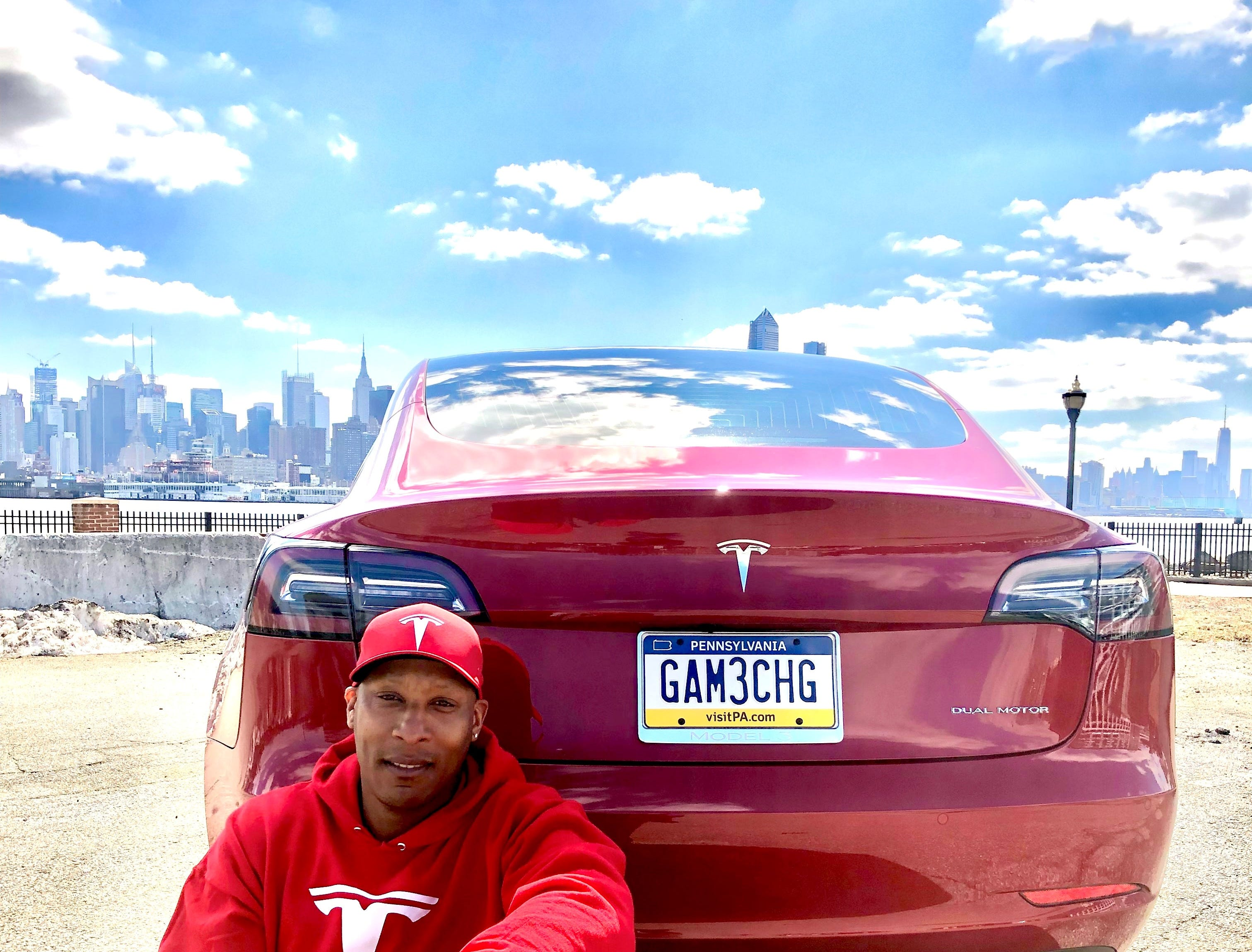 "Rodney Bailey, at the Hudson River in Weehawken, New Jersey, credits his Model 3 ""Tess"" with making him a better driver ""even though I thought I was pretty good prior to ownership."""