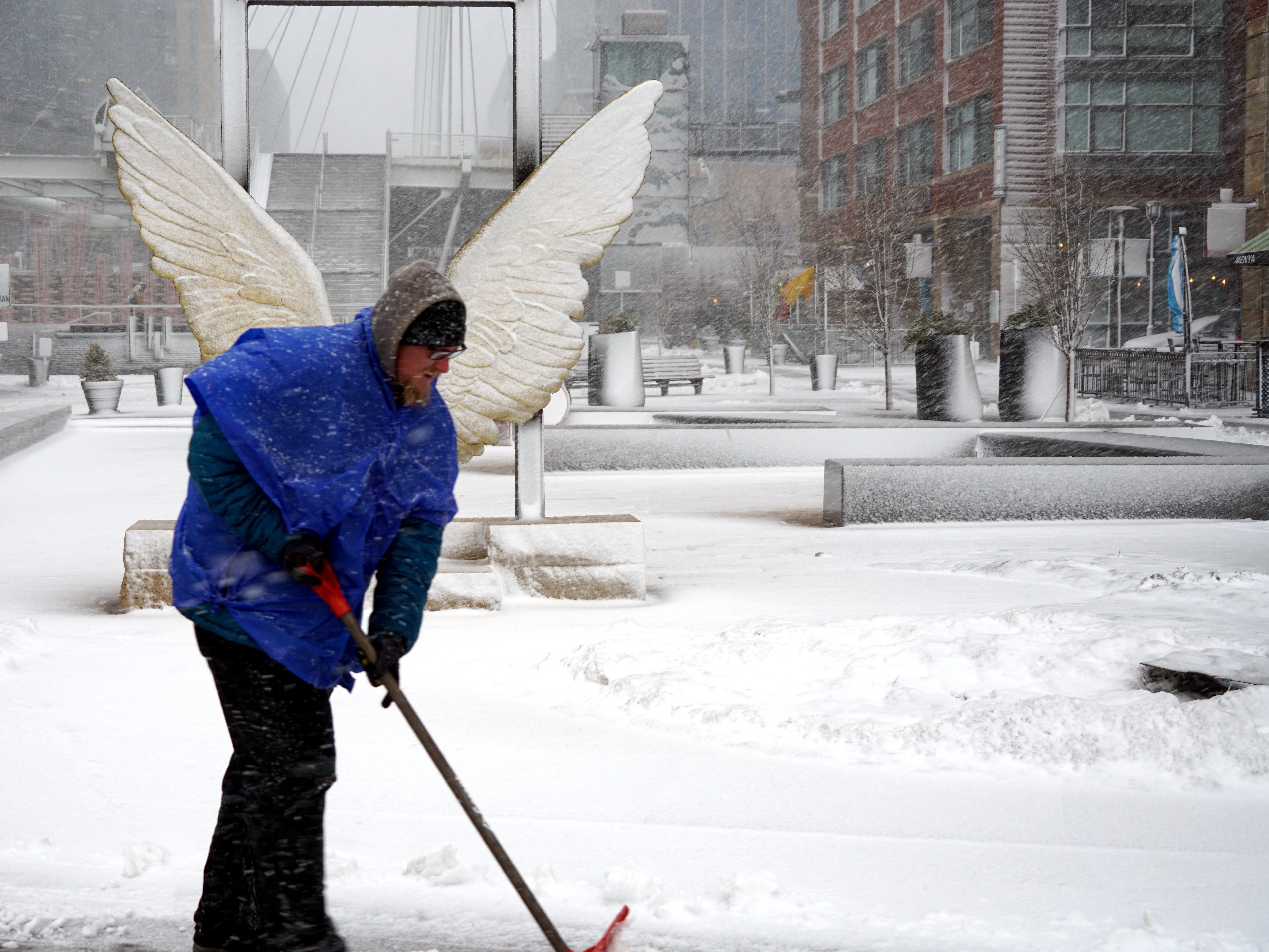Matt Krueger, 36, shovels snow near downtown Denver's Millennium Bridge during a blizzard, March 13, 2019.