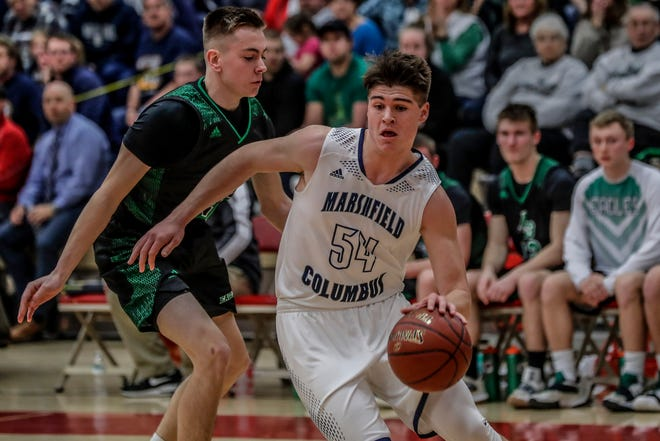 Columbus Catholic's Jarred Mandel (54) dribbles past Almond-Bancroft's Matt Lukas during WIAA Division 5 boys basketball sectional semifinal action March 7 in Wausau.