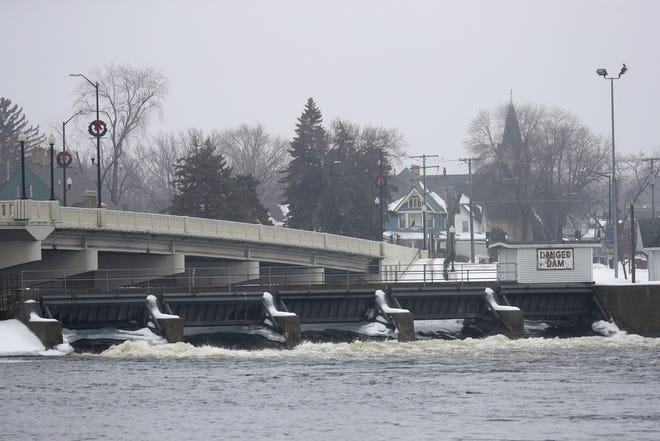 Water rushes through the Neenah dam Wednesday. The U.S. Army Corps of Engineers has the gates open to draw down Lake Winnebago in preparation for the spring snowmelt.