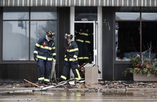 Firefighters pull a hose out of a stairwell after working to put out a structure fire in downtown Appleton on the corner of West Washington and North Appleton streets Wednesday.