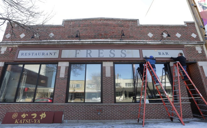 Fress is a new restaurant and bar opening in late March at 511 W. College Ave. in downtown Appleton. Here, Eagle Sign & Design's Dane DeValk, left, and Chris Hermann install its new signs.