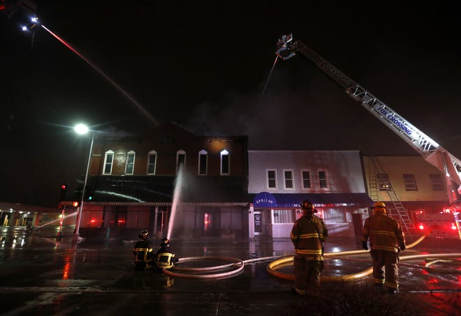 Firefighters work to put out a fire in Author's Kitchen + Bar, which is next door to Apollon.