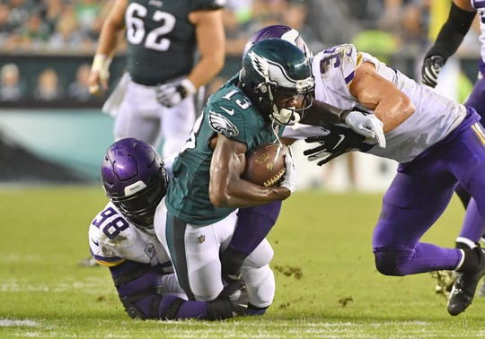 Philadelphia Eagles wide receiver Nelson Agholor (13) is tackled by Minnesota Vikings defensive tackle Linval Joseph (98) and strong safety Andrew Sendejo (34) during the fourth quarter at Lincoln Financial Field.