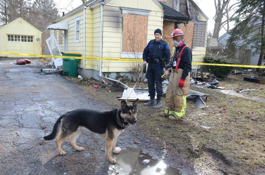 Michigan State Police Trooper Joel Service, left, and his dog, Baki, along with Battle Creek Fire Department Fire Marshal Quincy Jones searched the burned house on 32nd Street on Thursday.