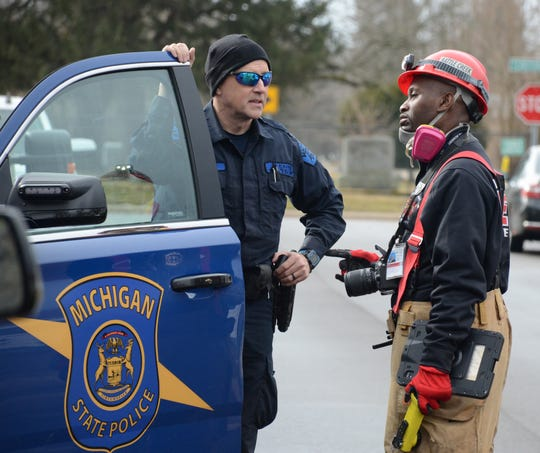 Fire Marshal Quincy Jones, right, talks with Trooper Joel Service after a search Thursday of the damaged home.
