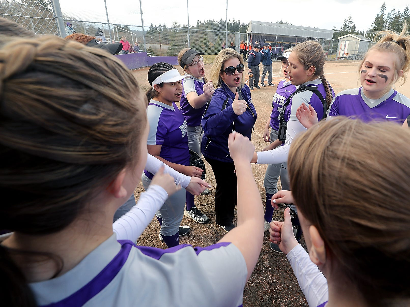 North Kitsap coach Jamie Smaaladen (center) joins her team in a cheer prior to the start of their game against Central Kitsap in Poulsbo on Wednesday, March 13, 2019.