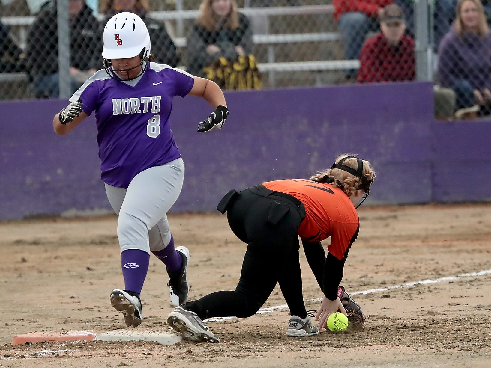 North Kitsap's Alicia Goetz is safe at first as Central Kitsap's Gabby Story misses the ball in Poulsbo on Wednesday, March 13, 2019.