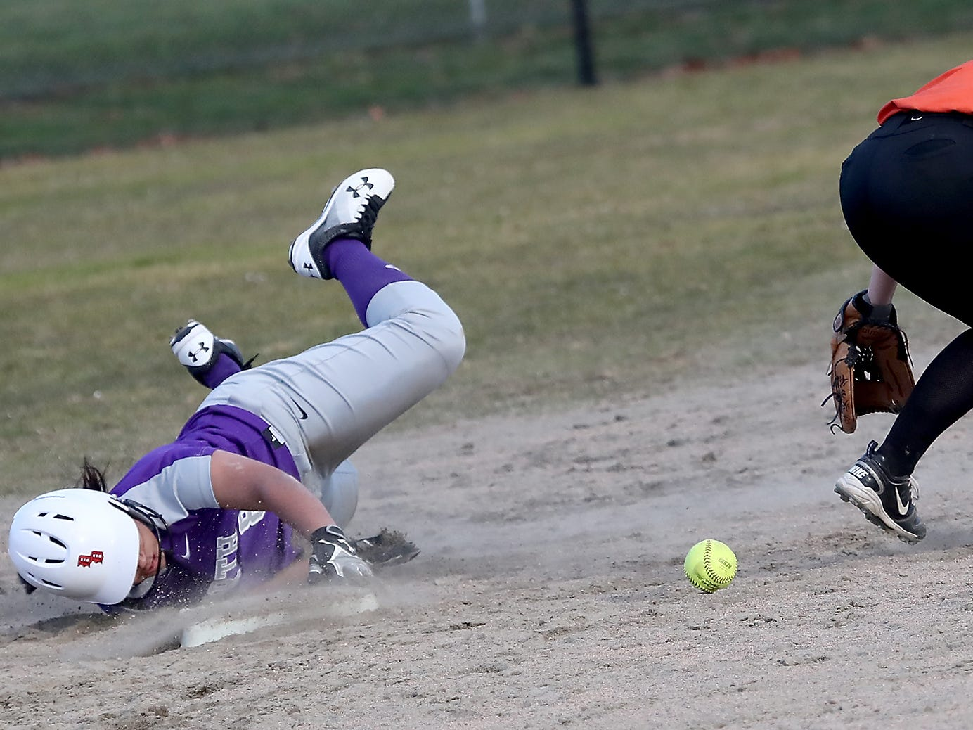 North Kitsap's Alicia Goetz slides into second as Central Kitsap's Brooke Mimaki tries to find the ball in Poulsbo on Wednesday, March 13, 2019.