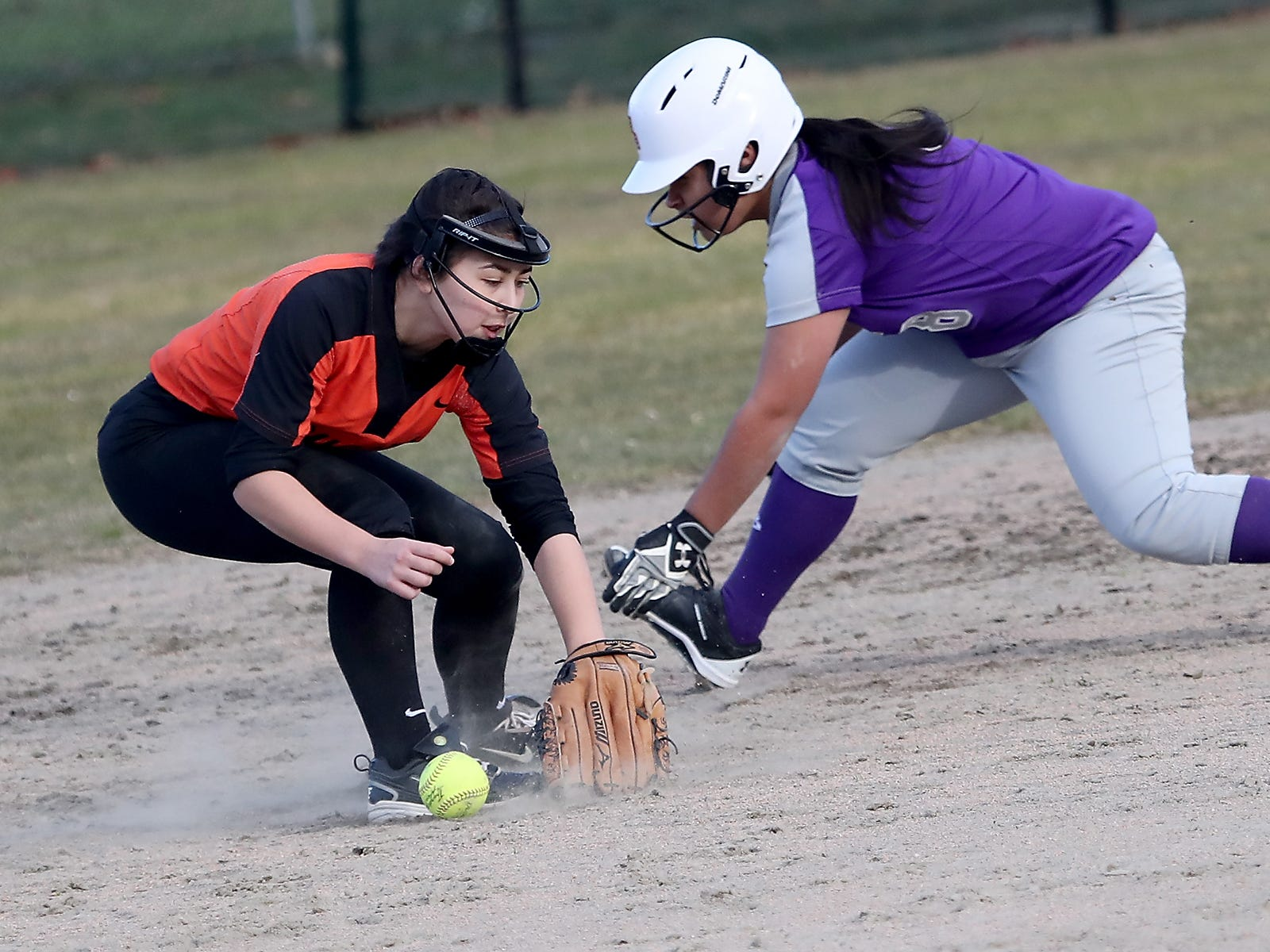 North Kitsap's Alicia Goetz gets ready to slide into second as Central Kitsap's Brooke Mimaki tries to find the ball in Poulsbo on Wednesday, March 13, 2019.