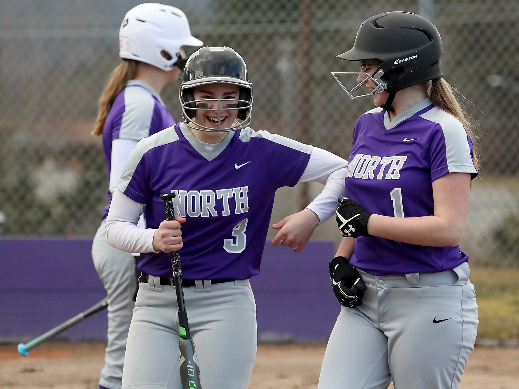 North Kitsap's Olivia Holmbry (3) and Samantha Burgh (1) celebrate a run against vs Central Kitsap in Poulsbo on Wednesday, March 13, 2019.