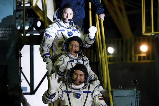 U.S. astronauts Christina Hammock Koch, centre, Nick Hague, above, and Russian cosmonaut Alexey Ovchinin, crew members of the mission to the International Space Station, ISS, wave as they board to the rocket prior the launch of Soyuz-FG rocket at the Russian leased Baikonur cosmodrome, Kazakhstan, Thursday, March 14, 2019.