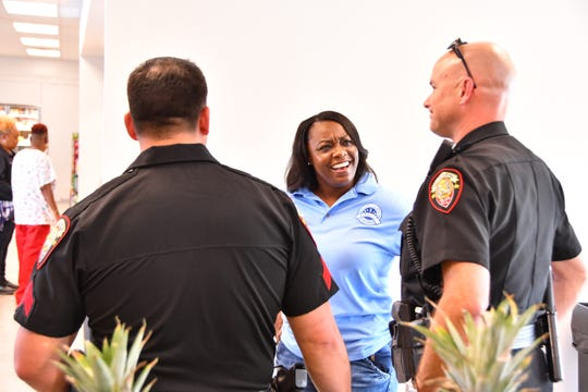 Kiwanda Brown, assistant manager of the Evans Community Market, talks with Melbourne PD Sgt. Jef Rau and Commander Marc Claycomb at the market. The newly opened Evans Center is on the border of Palm Bay and Melbourne, but actually in the city of Palm Bay. The police forces from the two cities have a joint enforcement agreement which allows both cities to go into surrounding areas in the area near the Evans Center.
