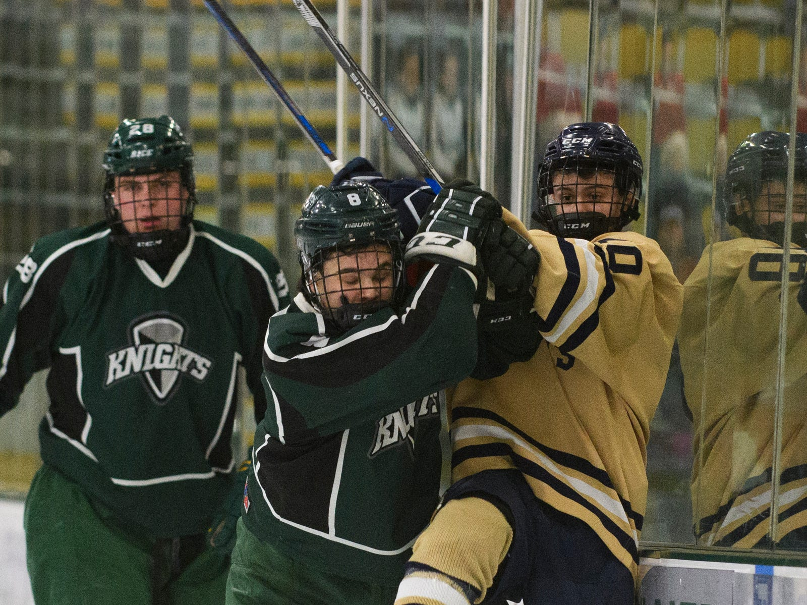 Rice's Cameron Kinsell (8) checks Essex's Charles Wiegand IV (10) into the boards during the DI boys hockey championship game between the Rice Green Knights and the Essex Hornets at Gutterson Field House on Wednesday night March 13, 2019 in Burlington, Vermont.
