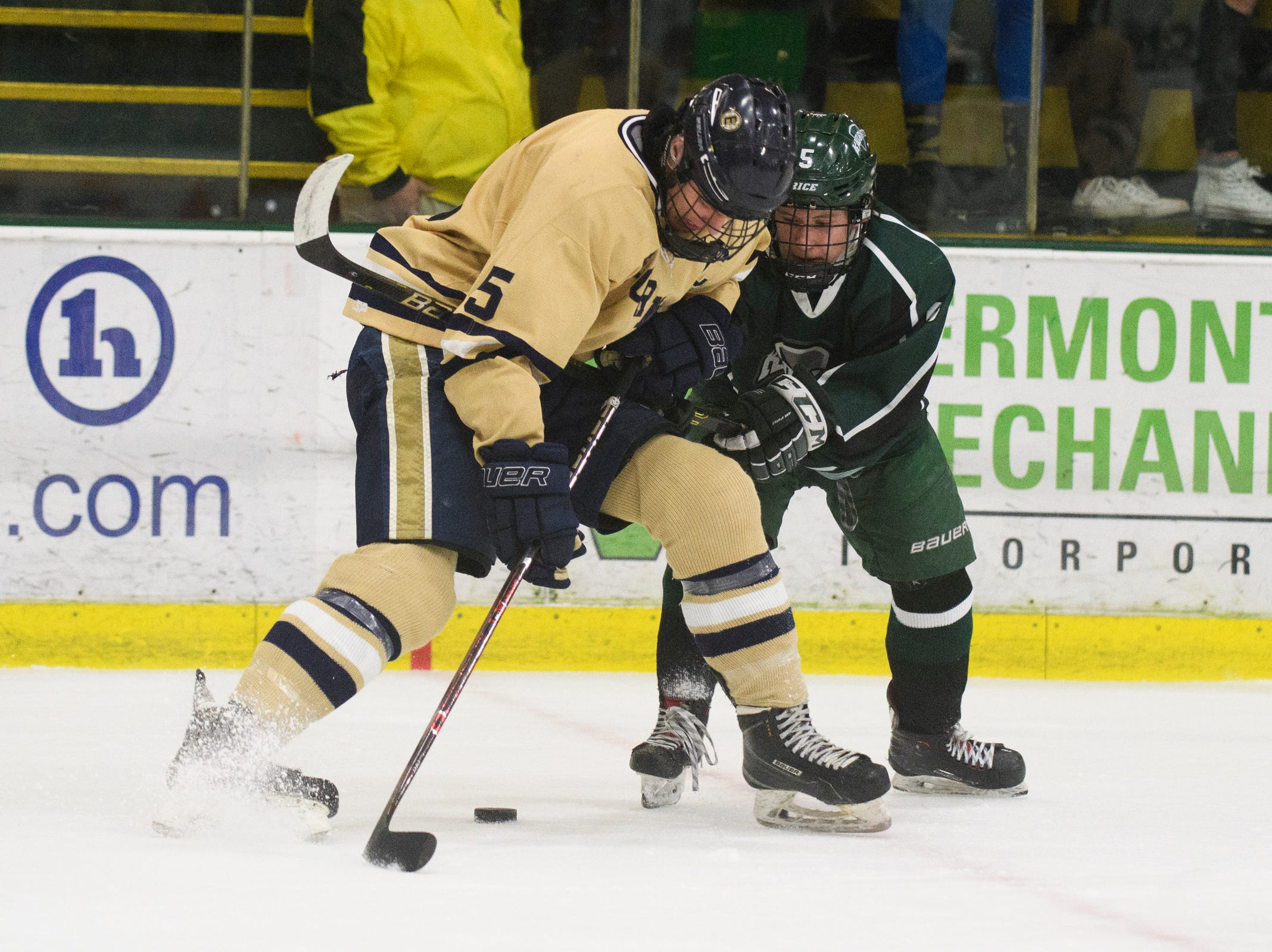 Rice's Connor Peet (5) battles for the puck with Essex's Jonah Janaro (5) during the DI boys hockey championship game between the Rice Green Knights and the Essex Hornets at Gutterson Field House on Wednesday night March 13, 2019 in Burlington, Vermont.