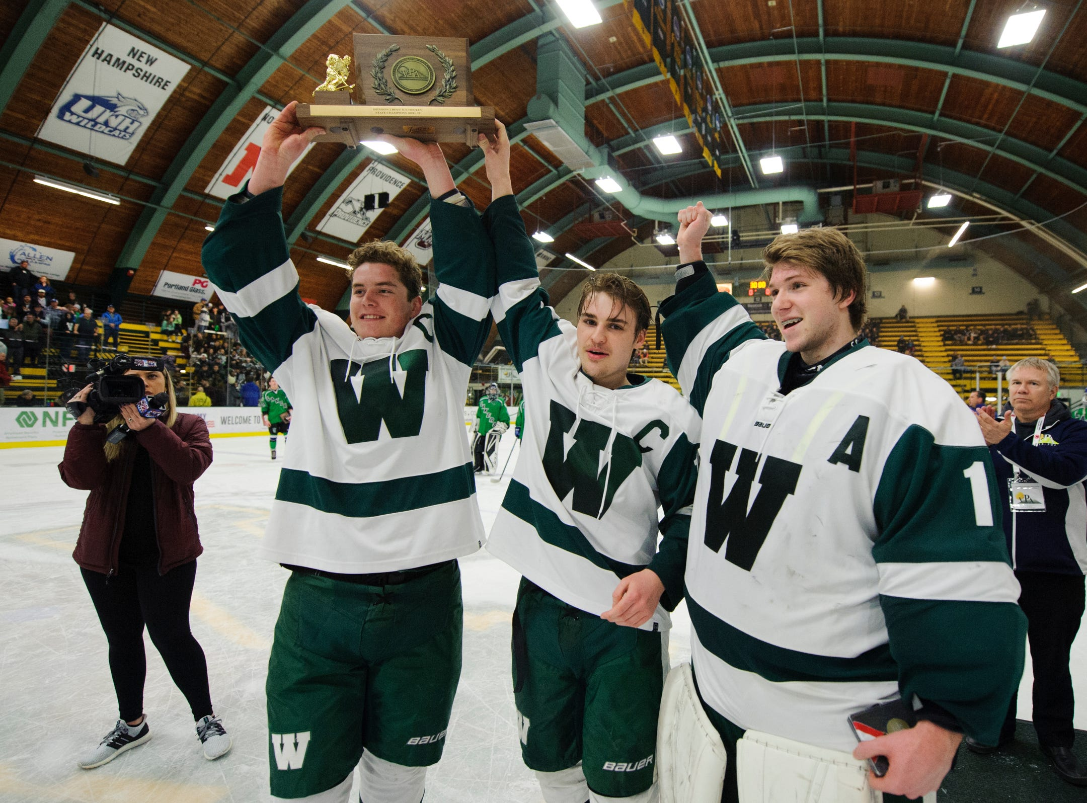 Woodstock captains hold up the championship trophy during the DII boys hockey championship game between the Woodstock Wasps and the Colchester Lakers at Gutterson Field House on Wednesday night March 13, 2019 in Burlington, Vermont.