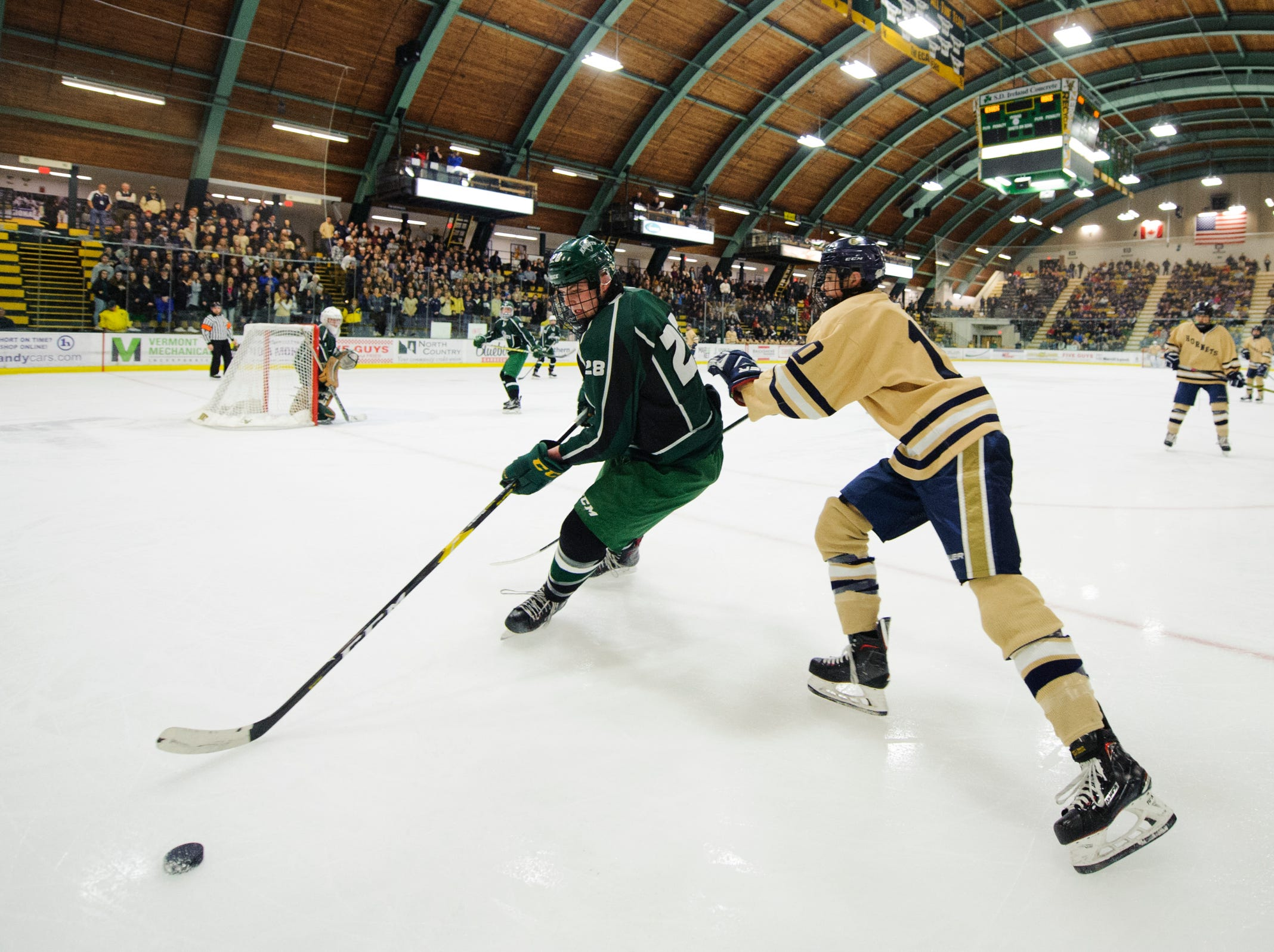 Rice's Kairan Connolly (28) skates with the puck past Essex's Charles Wiegand IV (10) during the DI boys hockey championship game between the Rice Green Knights and the Essex Hornets at Gutterson Field House on Wednesday night March 13, 2019 in Burlington, Vermont.