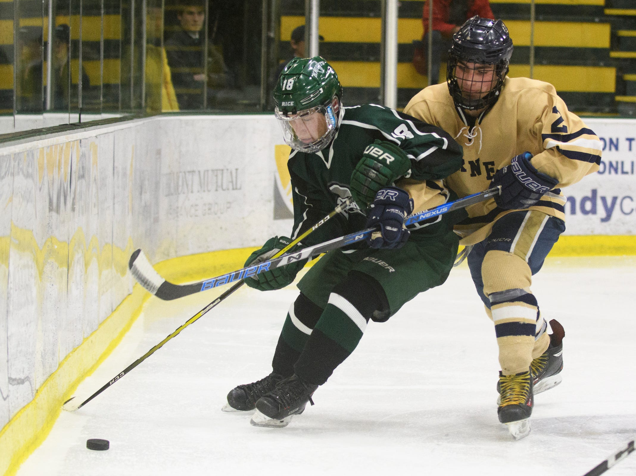 Essex's Grady Cram (2) battles for the puck with Rice's Sam Rubman (18) during the DI boys hockey championship game between the Rice Green Knights and the Essex Hornets at Gutterson Field House on Wednesday night March 13, 2019 in Burlington, Vermont.
