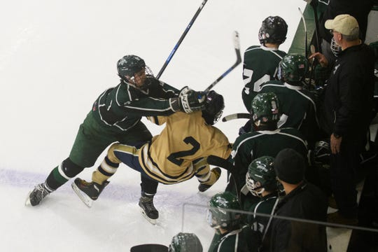Rice's Cameron Kinsell (8) checks Essex's Grady Cram (2) into the boards during the DI boys hockey championship game between the Rice Green Knights and the Essex Hornets at Gutterson Field House on Wednesday night March 13, 2019 in Burlington, Vermont.