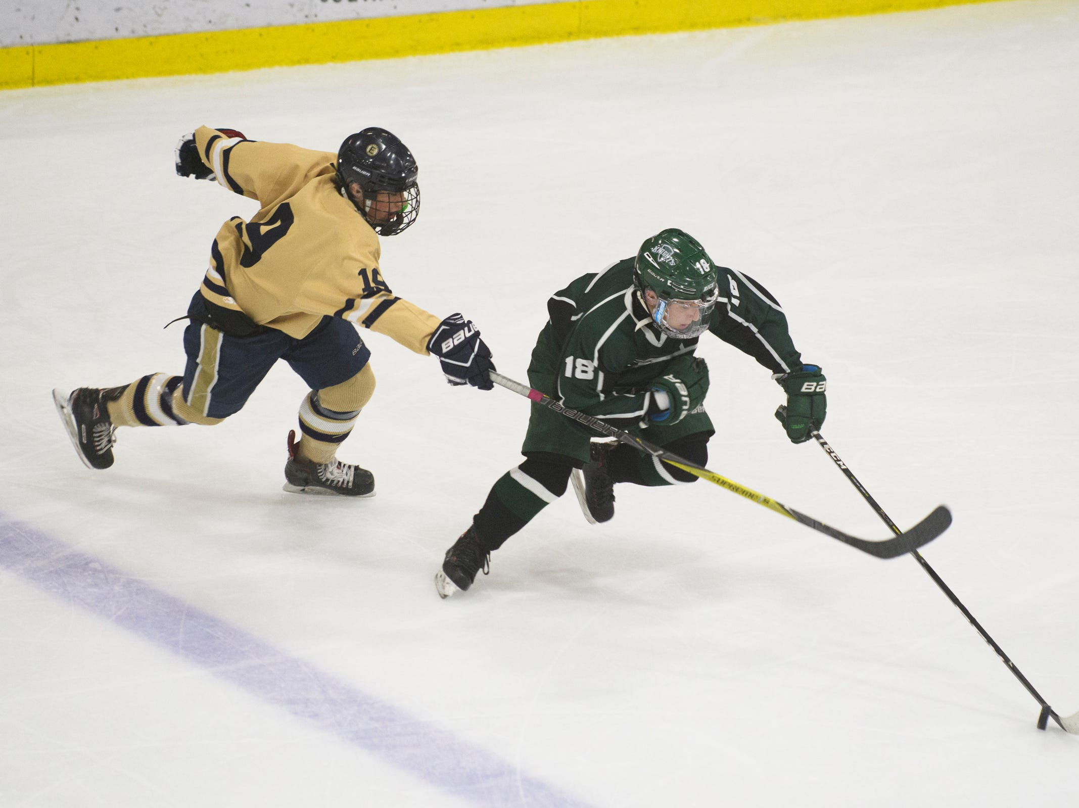 Rice's Sam Rubman (18) skates past Essex's Maxwell Line (19) with the puck during the DI boys hockey championship game between the Rice Green Knights and the Essex Hornets at Gutterson Field House on Wednesday night March 13, 2019 in Burlington, Vermont.