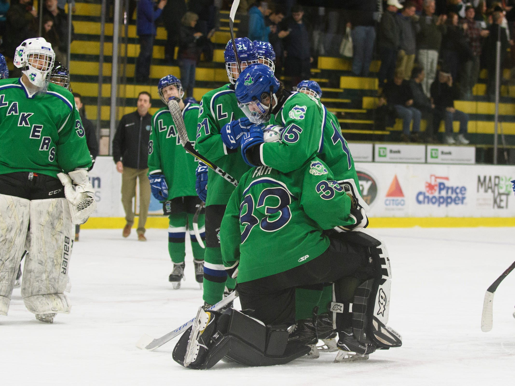 Colchester's Andy Roast (15) hugs goalie Sam Fath (33) at the conclusion of the DII boys hockey championship game between the Woodstock Wasps and the Colchester Lakers at Gutterson Field House on Wednesday night March 13, 2019 in Burlington, Vermont.