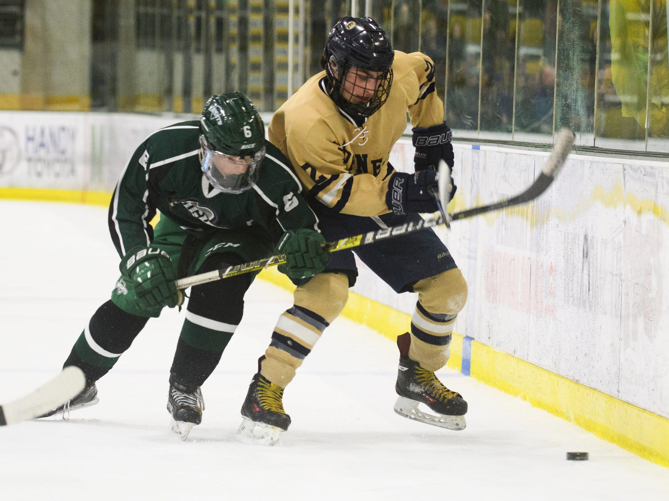 Rice's Jackman Hickey (6) battles for the puck with Essex's Grady Cram (2) during the DI boys hockey championship game between the Rice Green Knights and the Essex Hornets at Gutterson Field House on Wednesday night March 13, 2019 in Burlington, Vermont.
