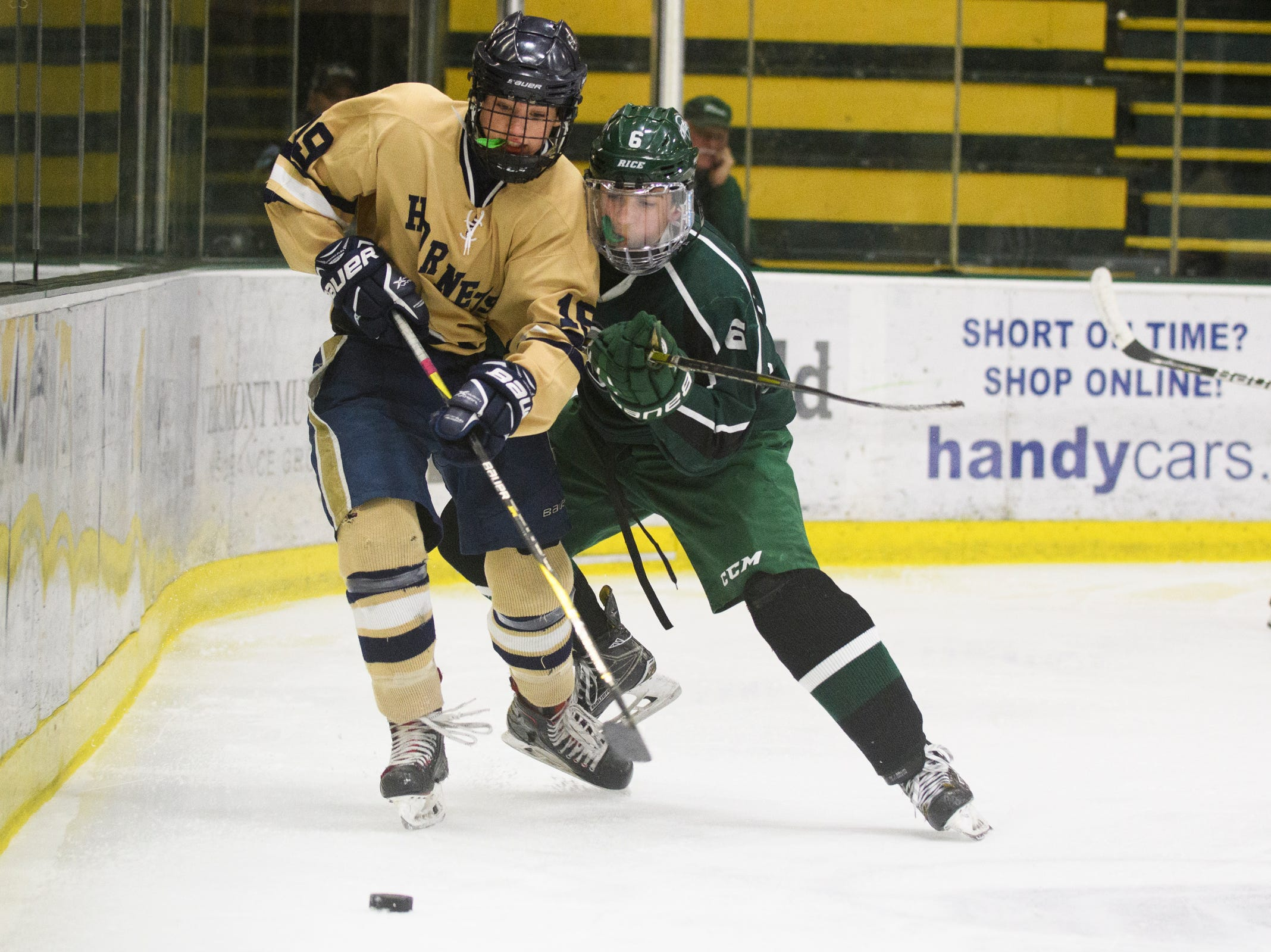 Rice's Jackman Hickey (6) battles for the puck with Essex's Maxwell Line (19) during the DI boys hockey championship game between the Rice Green Knights and the Essex Hornets at Gutterson Field House on Wednesday night March 13, 2019 in Burlington, Vermont.