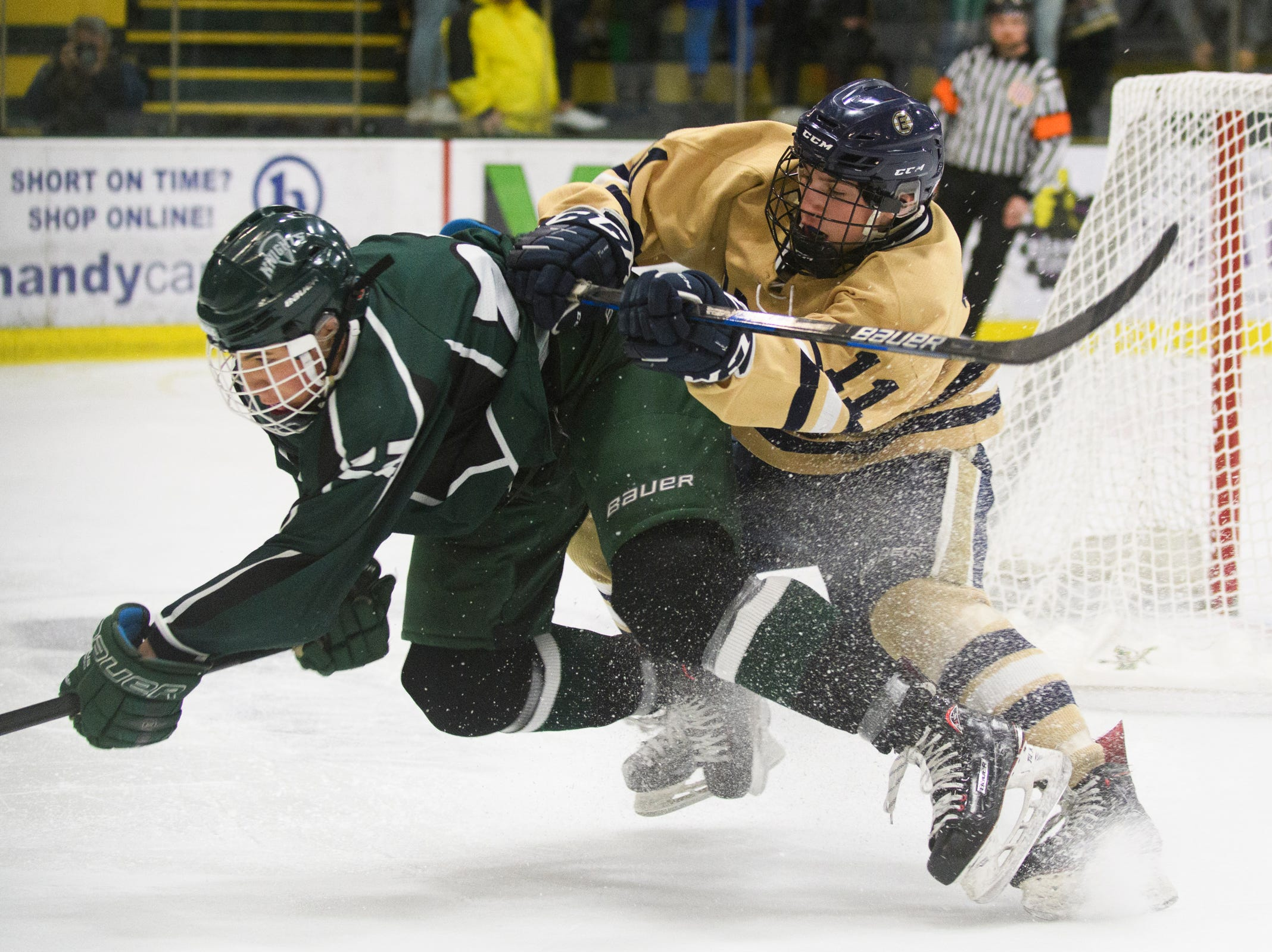 Rice's Will Crawford (13) and Essex's Ryan Clark (11) battle for the puck during the DI boys hockey championship game between the Rice Green Knights and the Essex Hornets at Gutterson Field House on Wednesday night March 13, 2019 in Burlington, Vermont.