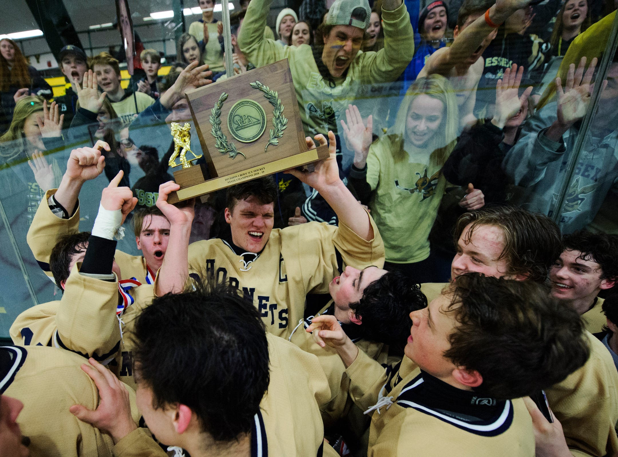 Essex celebrates with the championship trophy during the DI boys hockey championship game between the Rice Green Knights and the Essex Hornets at Gutterson Field House on Wednesday night March 13, 2019 in Burlington, Vermont.