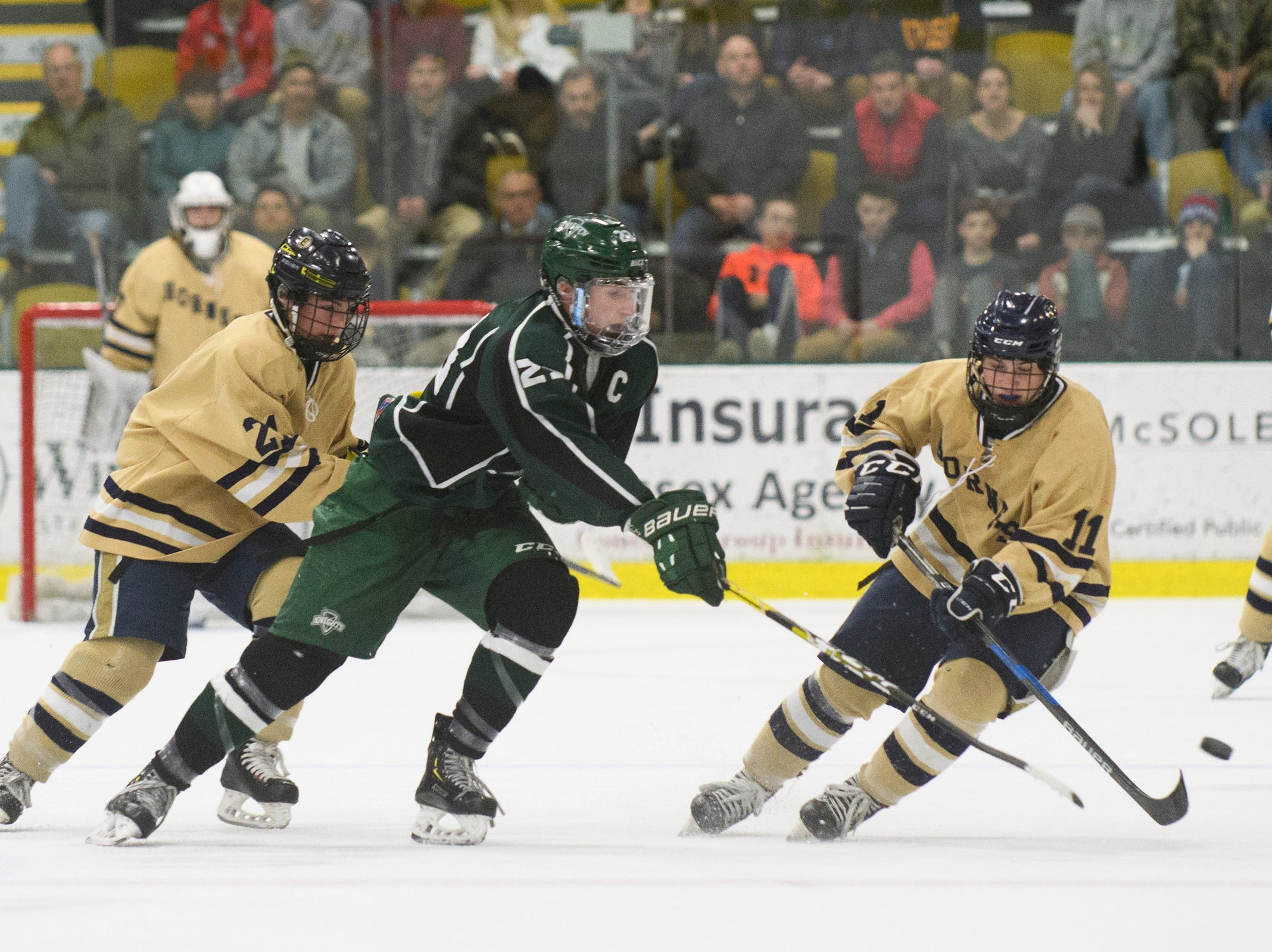Rice's Reilly Hickey (23) battles for the puck with Essex's Ryan Clark (11) during the DI boys hockey championship game between the Rice Green Knights and the Essex Hornets at Gutterson Field House on Wednesday night March 13, 2019 in Burlington, Vermont.