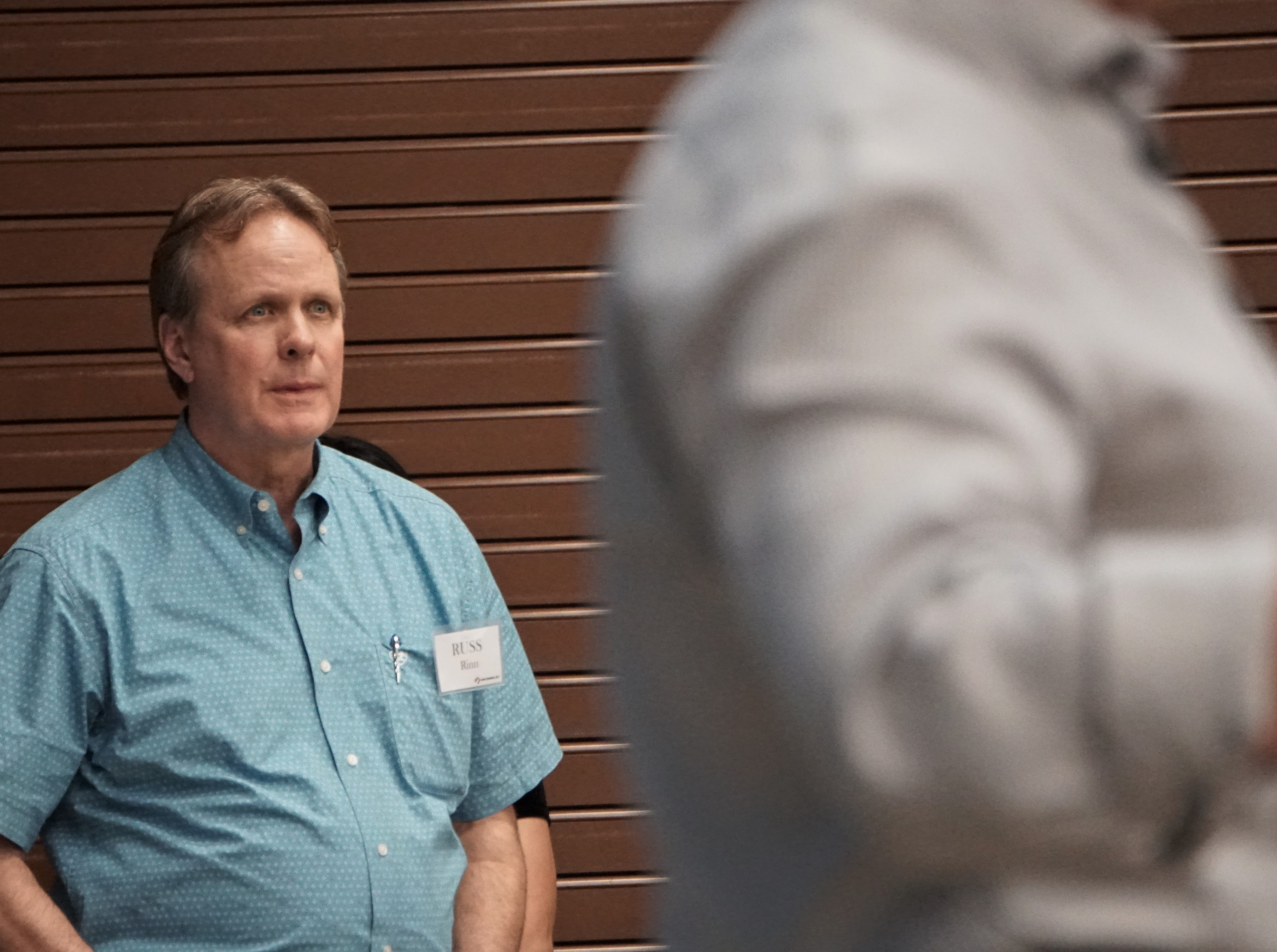Russ Rinn, executive vice president of metals recycling for Steel Dynamics, listens as the company's CEO, Mark Millett, addresses the audience during a meet and greet at the San Patricio County Civic Center in Sinton on March 13, 2019.