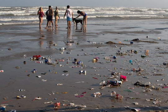 Trash fills the beach after a large group of spring breakers in broken up on the beach in Port  Aransas on Wednesday, March, 13, 2019.